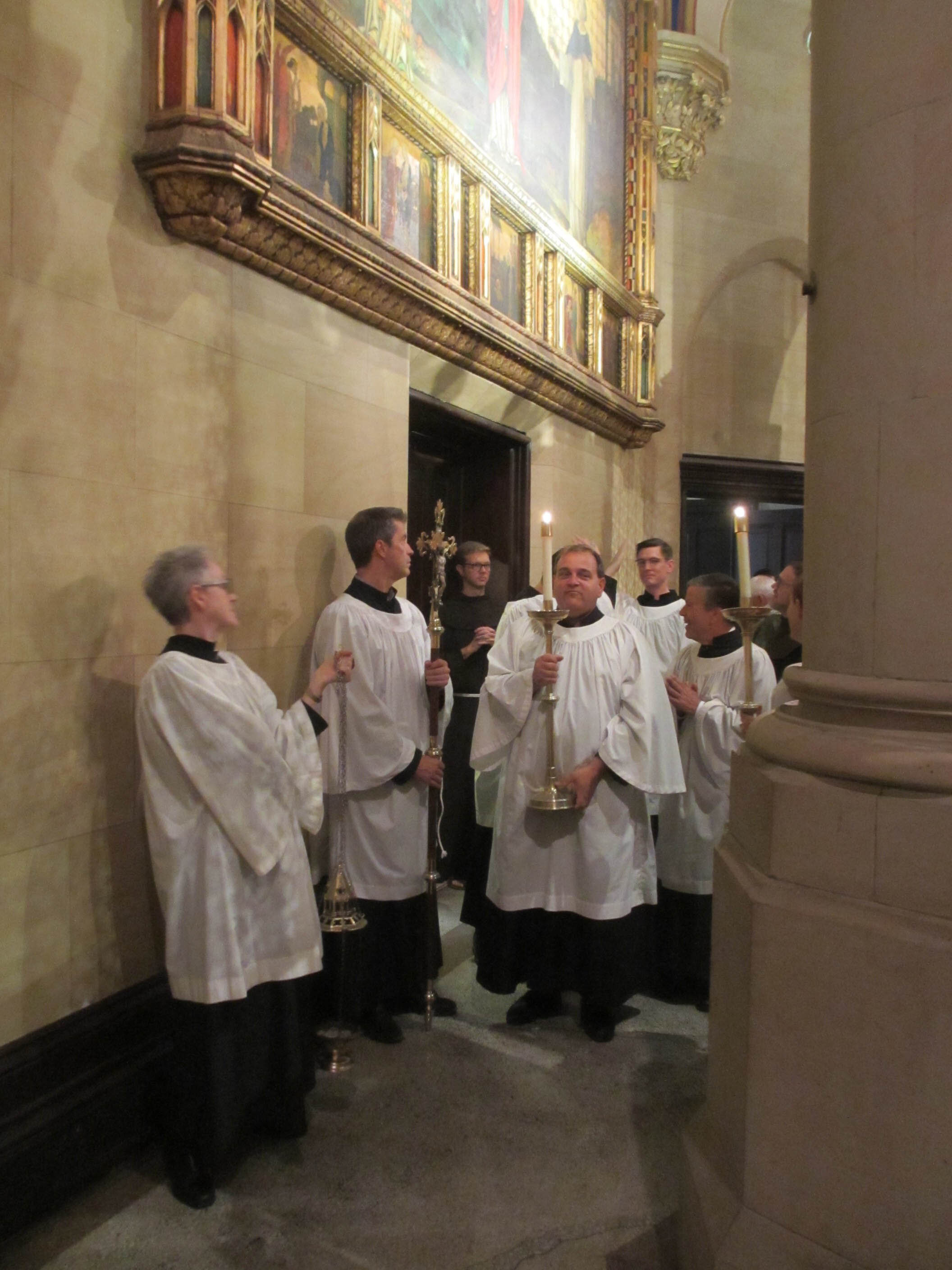 Smiles and a few whispers as the ministers of the liturgy gather behind the altar while the organ prelude concludes.    Photo:  MaryJane Boland