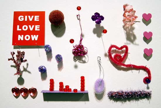 "GIVE.LOVE.NOW.  , 2008 (for Kate Spade) Paper, plastic, laser print, acrylic paint, wire, aluminum, pipe cleaner, sequins, nail enamel, glitter and straight pins on drywall, 12"" x 8-1/2"" x 1-3/4"""