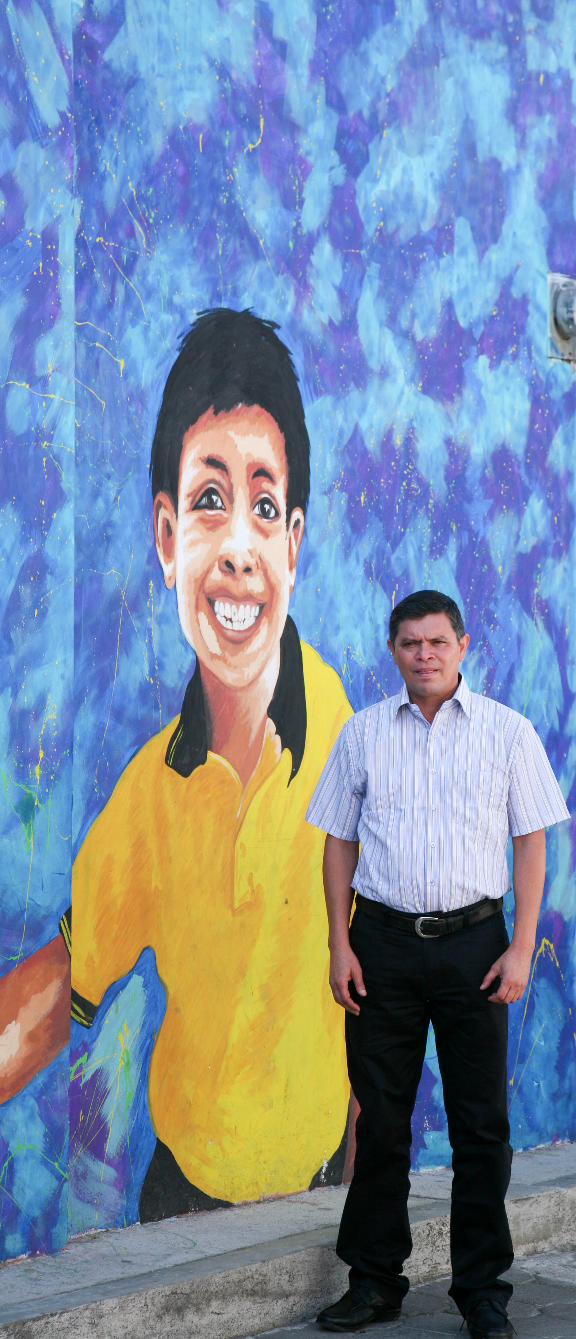 Julio Garcia, in front of school mural