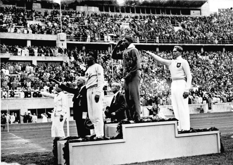 A photo of  Jesse Owens  standing on the medal podium with others doing the Nazi salute around him (WikiCommons).