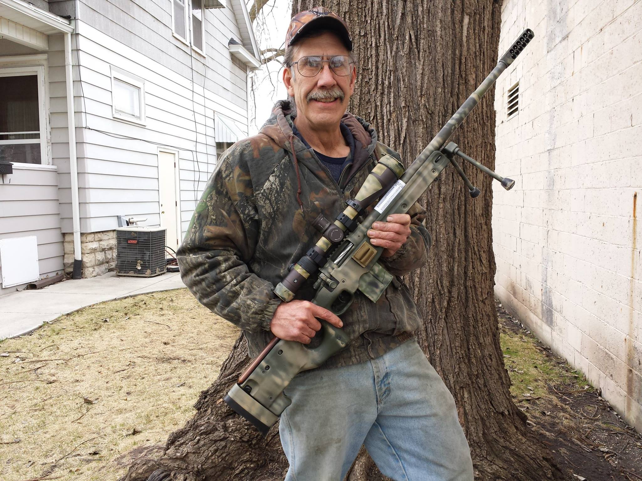 John Huber showing off his rifle next to the shop!