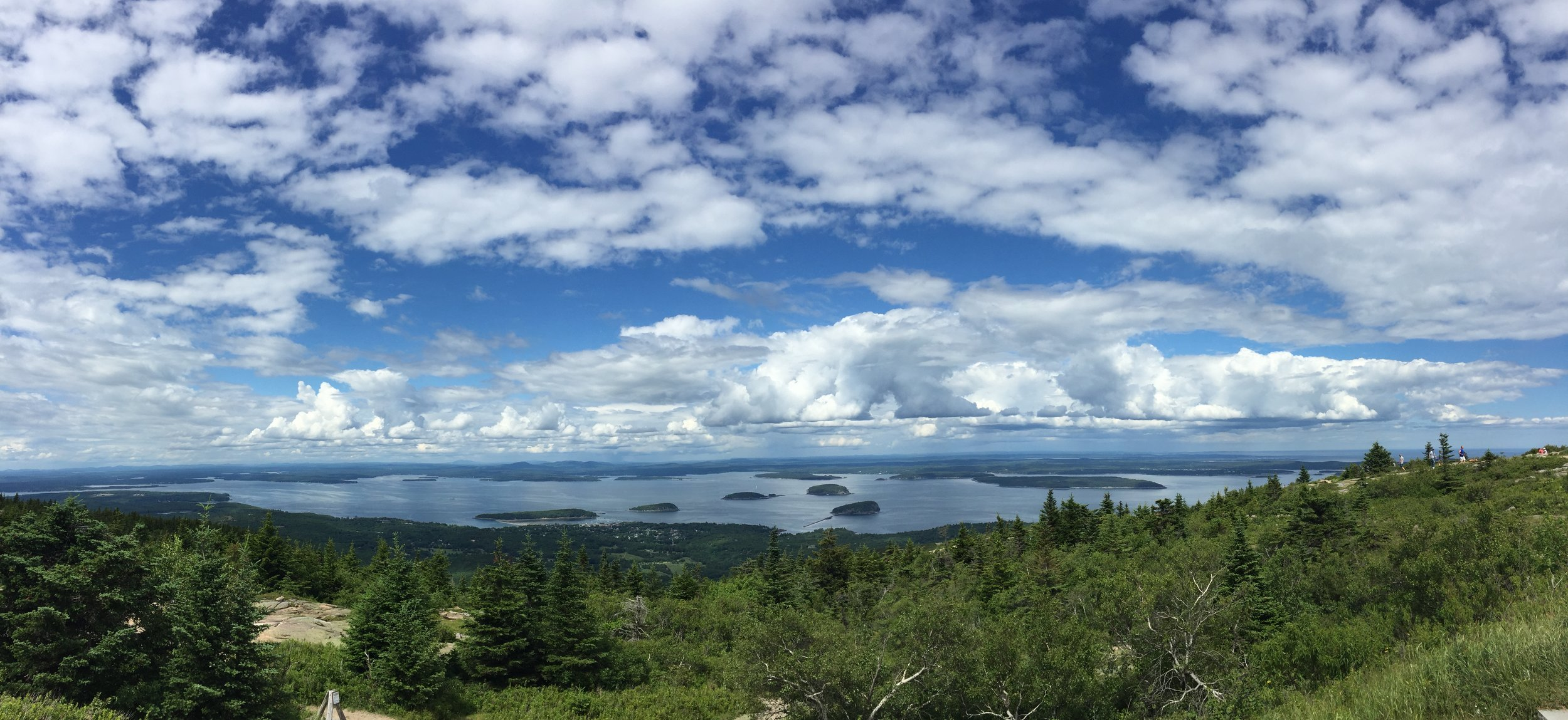 This photo displays the view from atop Cadillac Mountain in Acadia National Park in Bar Harbor, Maine. Peering across the Frenchman Bay, spotted with many little islands, we seemed to be standing above the clouds.