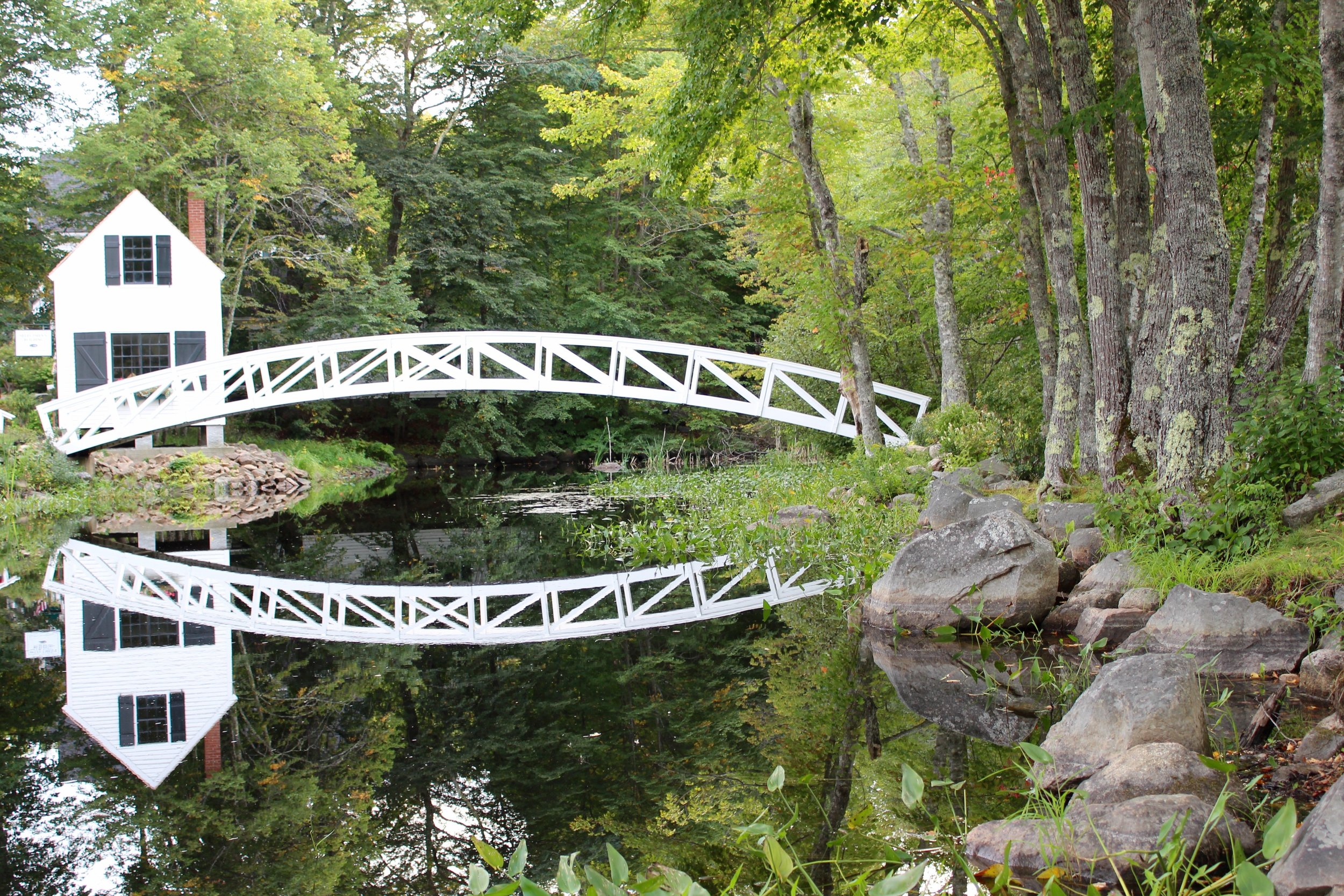 While we are trying not to pick a favorite, this photo just might be our best of the year. That near perfect reflection of that beautiful, old wooden bridge along with the green foliage of Somesville, Maine.