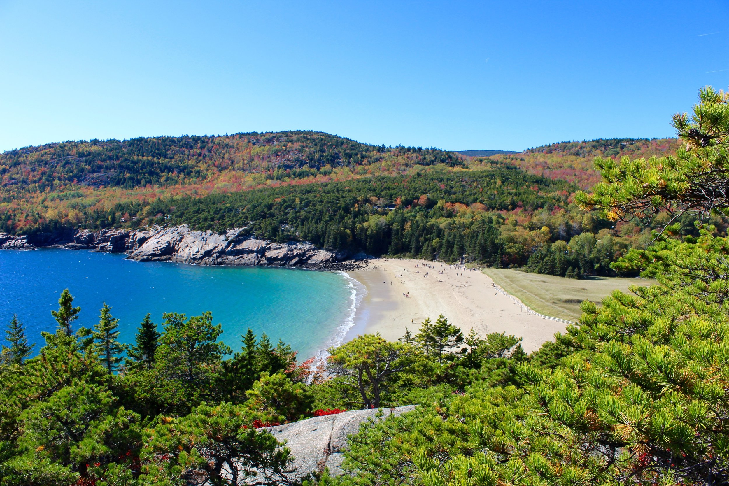 From the edge of Great Head in Acadia National Park in Bar Harbor, Maine we are rewarded with the view of Sand Beach and the mountains of Acadia. The green of the evergreen mixed with the fall colors of the deciduous trees complete the frame of this photo.