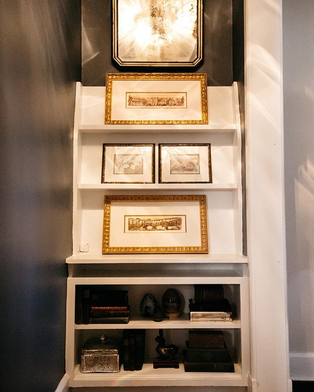 Our client had an existing display shelf in a passthrough that she didn't know what to do with.  We added a gorgeous antique etched mirror to add height, some newly framed art from her travels, and styled the shelving below with existing books and decor. What was an unused space, now holds treasured pieces that she walks by daily.
