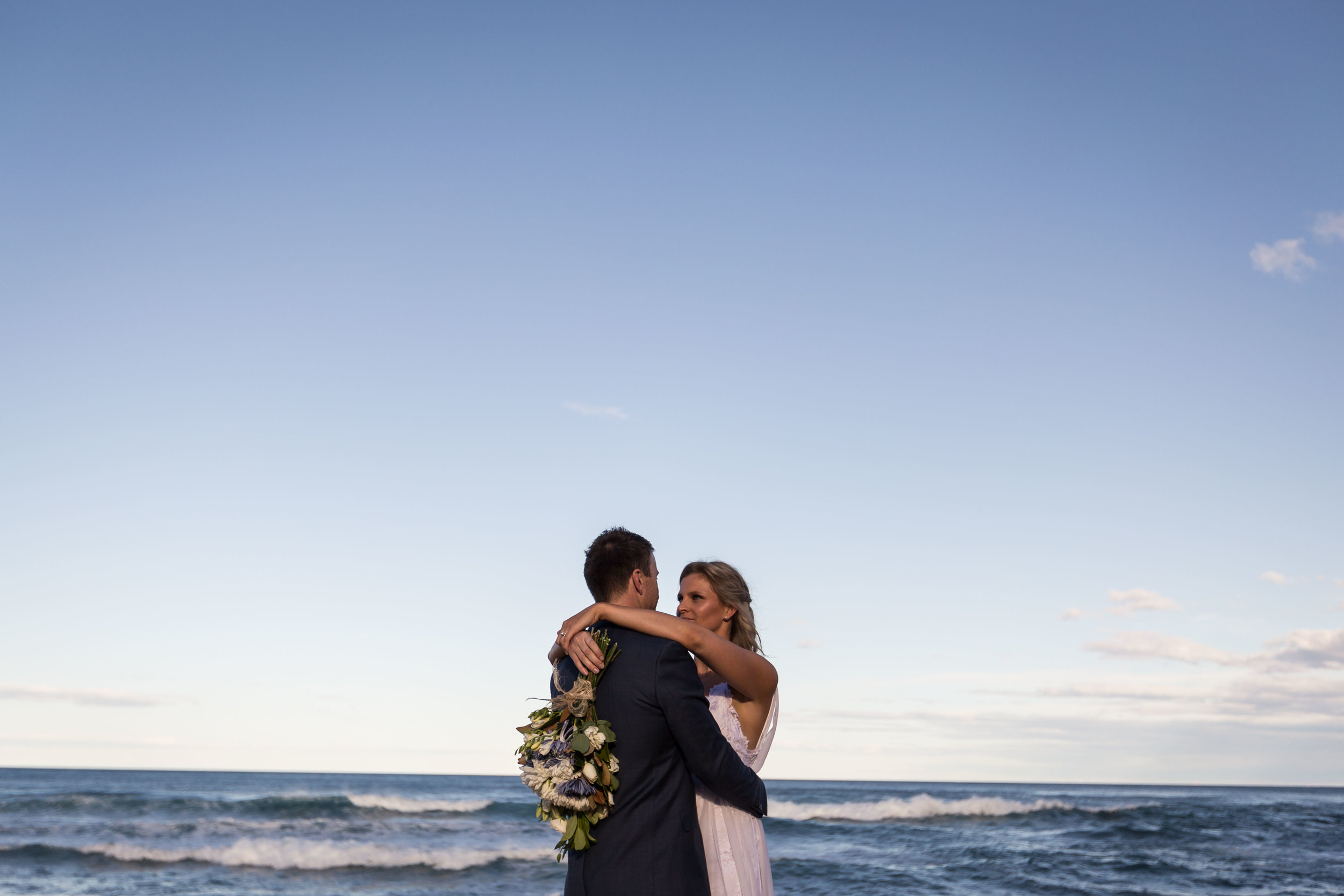 Bride and groom on the beach at dusk. Bilgola Beach wedding.