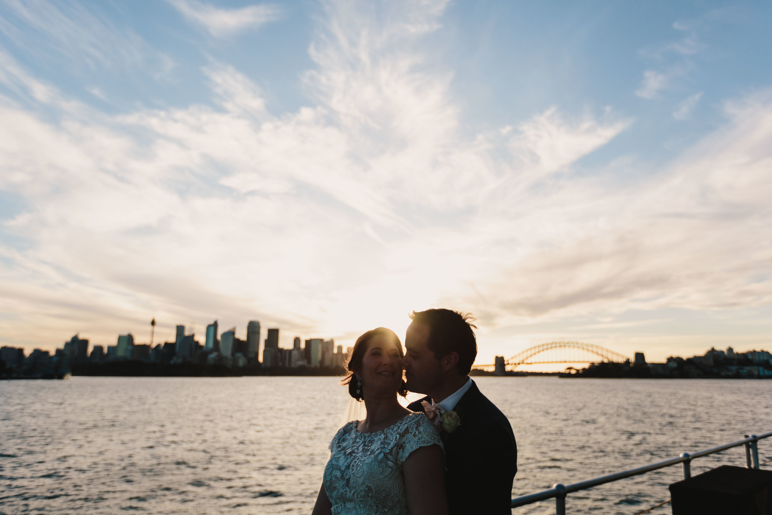 Bride and groom on Sydney harbour at sunset. Relaxed, candid wedding photography. Sydney wedding.