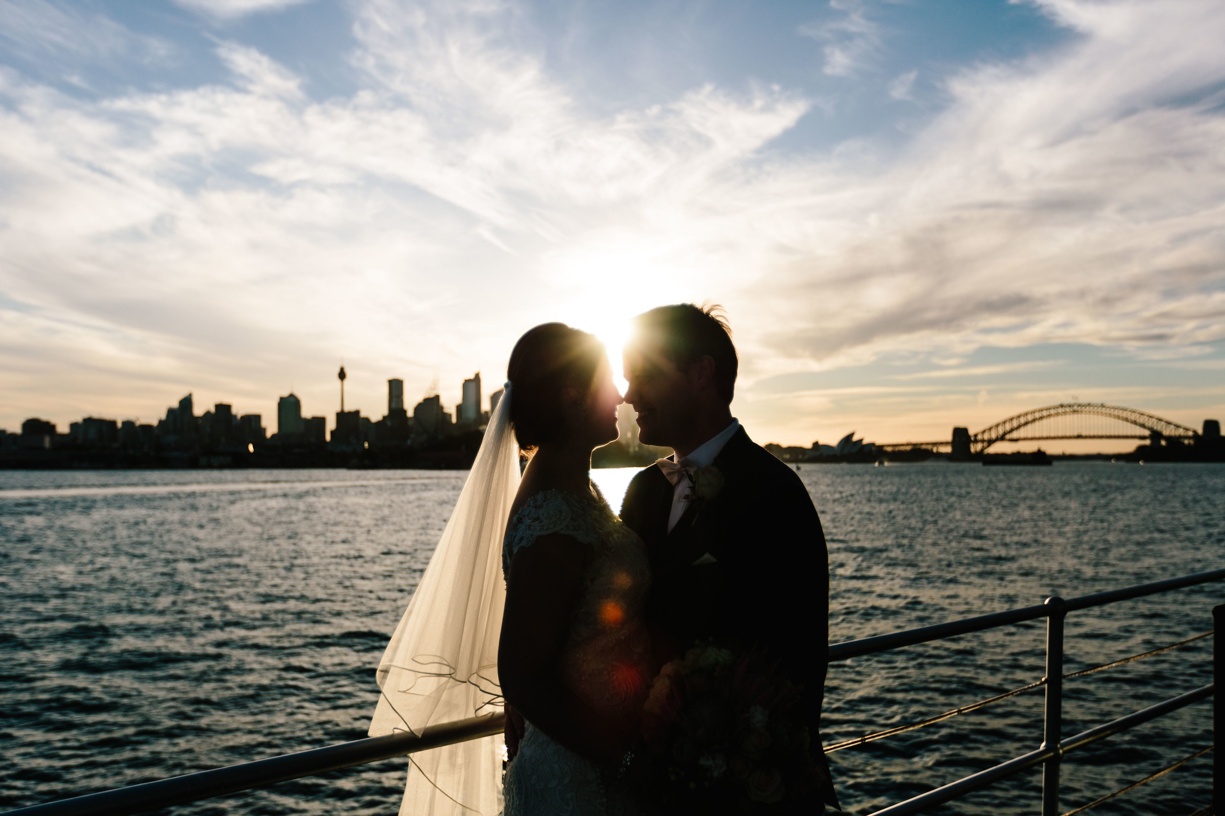 Bride and groom kissing at sunset. Sydney harbour wedding