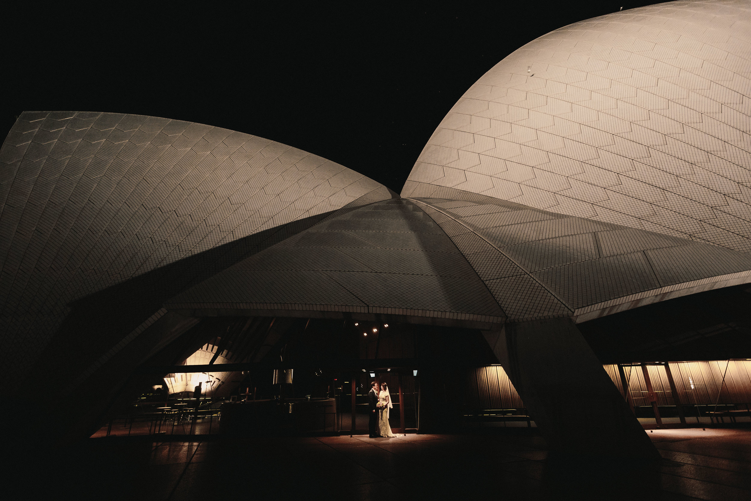 Bride and groom under the Sydney Opera House. Sydney Harbour Wedding