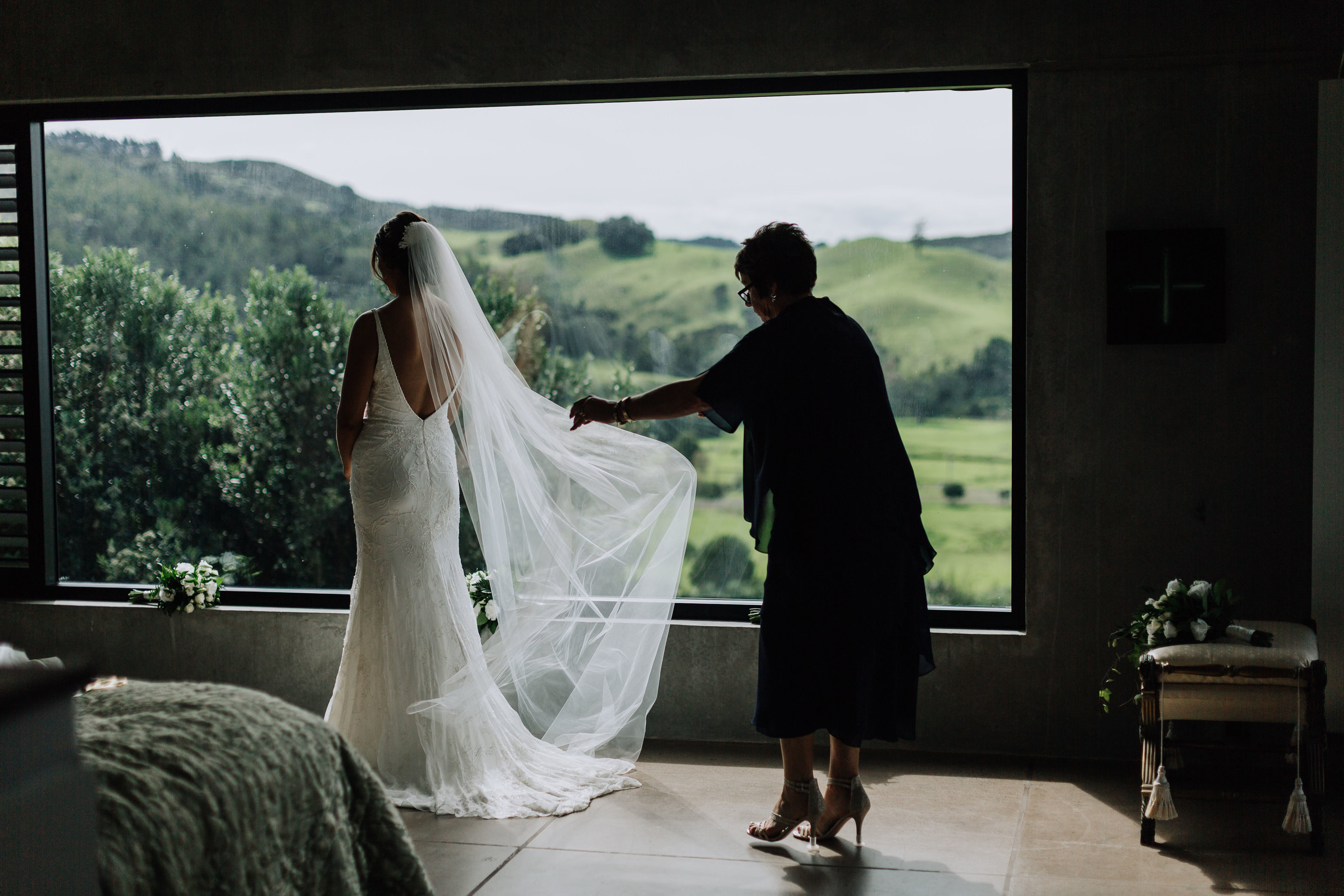 Mother of the bride dressing daughter. Coromandel Coast Wedding. New Zealand Photographer