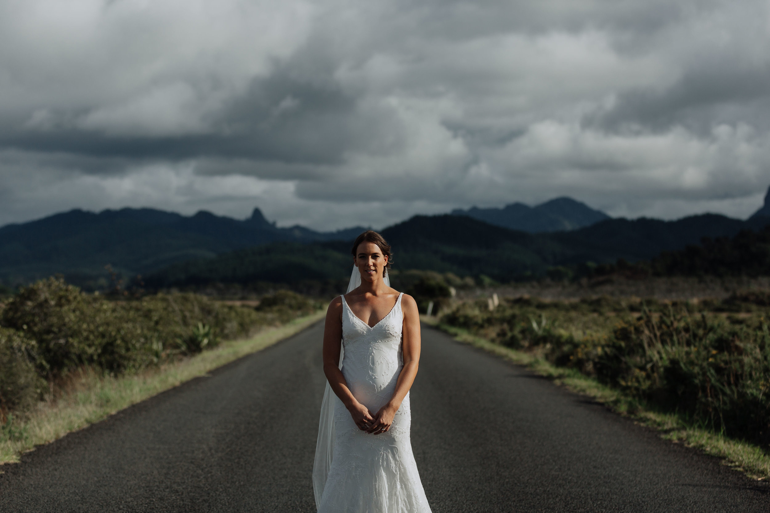 Bride on a country road in New Zealand. Coromandel Coast wedding