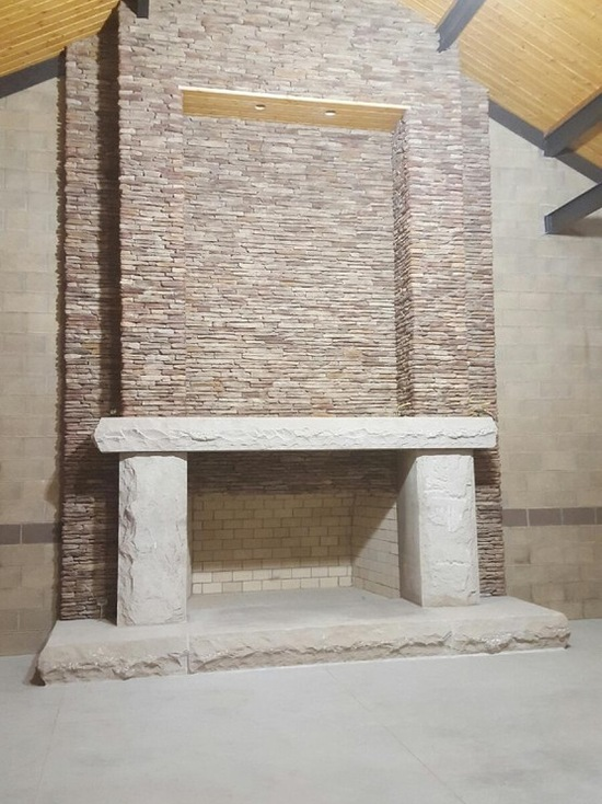 unfinished massive stone fireplace indoors