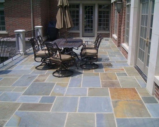 natural stone patio in a backyard with patio furniture