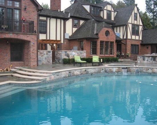 Luxury brick tudor style home with backyard patio and pool