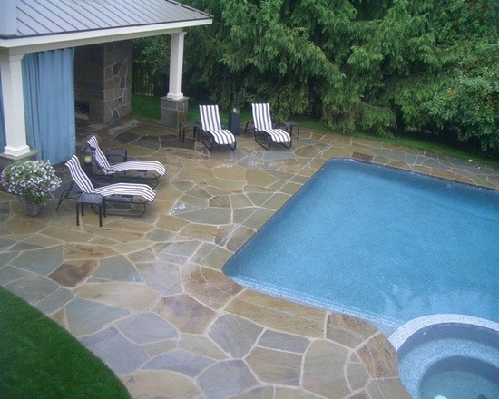 Chaise chairs and outdoor covered patio with natural stone deck and pool