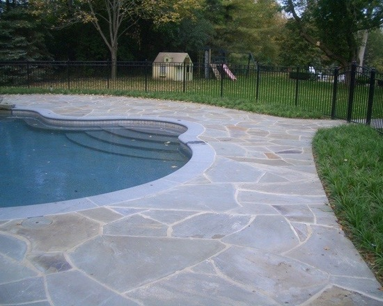 Shallow end of pool in backyard stone deck