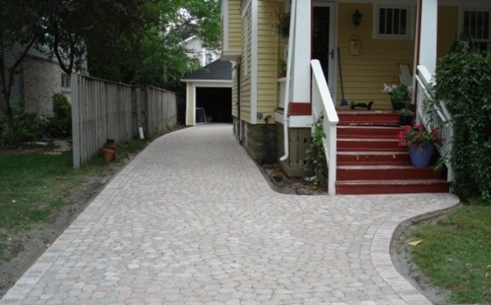 Brick driveway and brick steps in front of yellow house with front porch