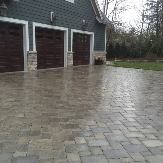 Three car garage with wooden doors and brick driveway