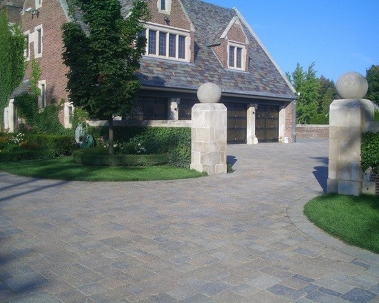 Brick luxury home with stone wall guarding brick driveway