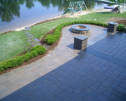 Brick patio and firepit next to a lake