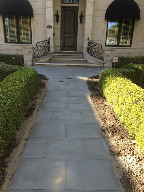 Large brick walkway to house lined with hedges