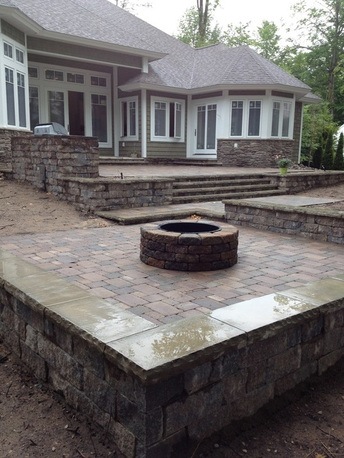 natural stone patio with circular firepit in the backyard