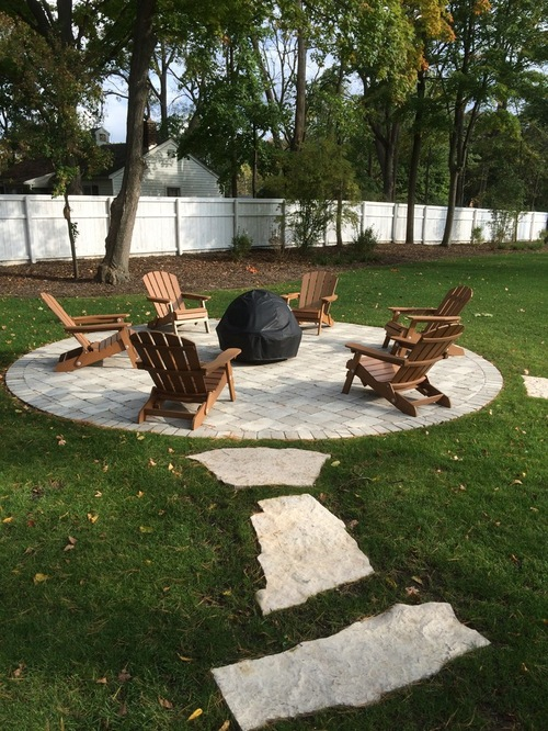 drone tiles leading to a circular outdoor patio in the backyard with adirondak chairs surrounding a firepit