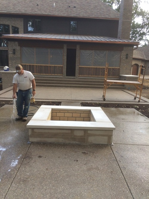Man in construction working on a square firepit on a patio