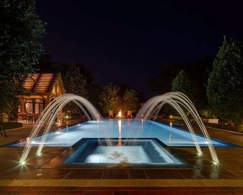 Custom firepit and pool scene in backyard at night