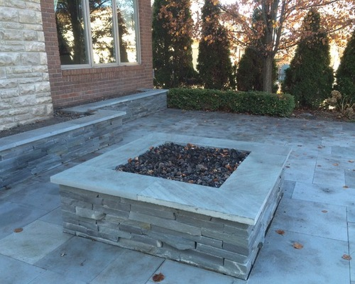 Square stone fireplace on natural stone patio