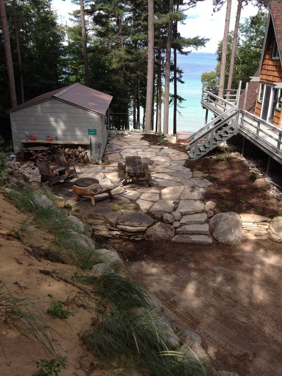 rustic cabin with natural stone deck and chair overlooking lake