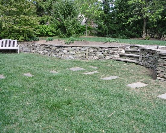 grassy backyard with low stone wall