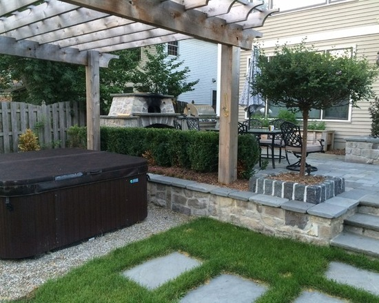 backyard hot tub under pergola with outdoor kitchen