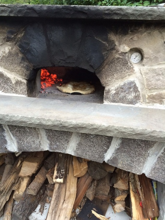 pizza oven with wood storage and fire burning
