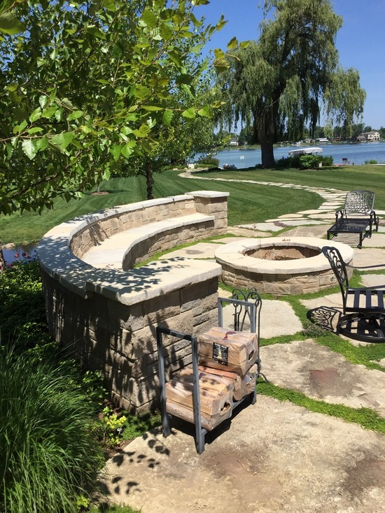 stone bench surrounding firepit and outdoor kitchen
