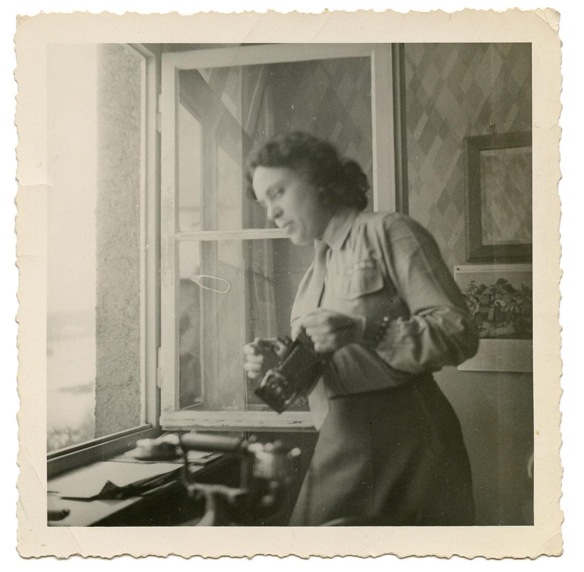 "Uniformed woman & camera. B&W print, undated, 3.5"" x 3.5"" Found in Philadelphia, PA"