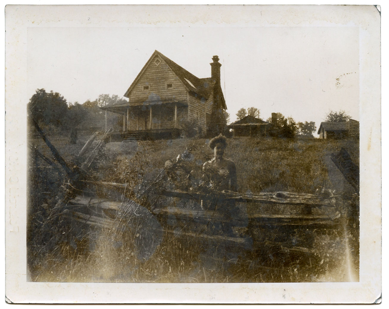 """Woman infront of an old farm house (with a skylight? or?). Polaroid, Approximately 1996. 3.25"""" x 4.25"""" Found in Philadelphia, PA   While I previously thought this Polaroid was older, according to  this document  published by Polaroid in 1998, it is from the 1990's. Based on the code on the back, H6V010201H, it is from a pack of B&W 667 coaterless film (10 frames) and was made in Scotland (Vale of Leven) in 1996.  What appears to be sepia tone is discoloration and slight mirroring, which can be attributed to a number of things but mainly the inherent instability of the Polaroid format (though some instant films are more stable than others) Above all else, it has probably suffered some deterioration due to how it has been stored. After all, I found it in a plastic storage bin at a reuse center."""