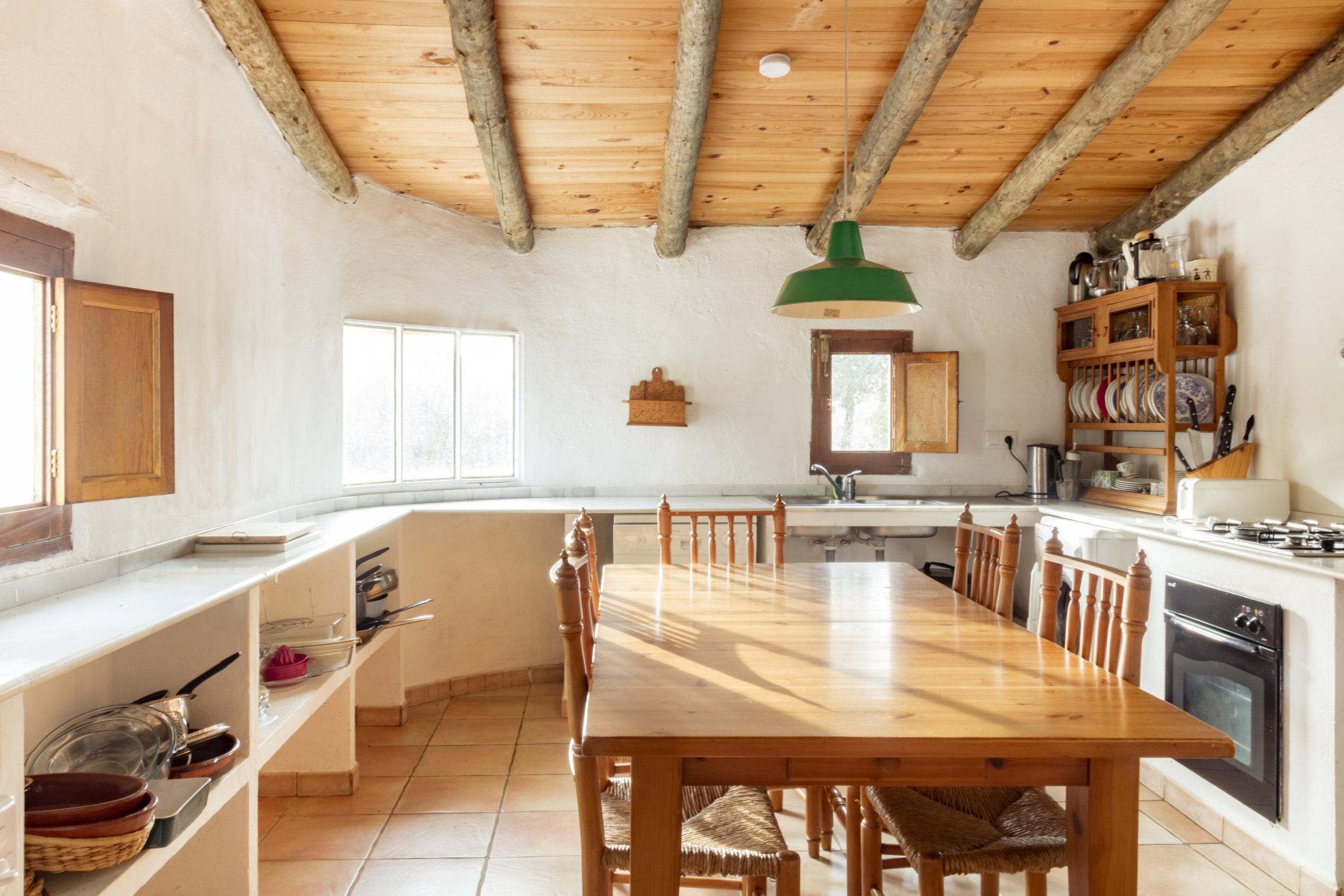 La cuisine das la maison de Luis. Table et chaises en bois, surfaces de travail en marbre blanc.