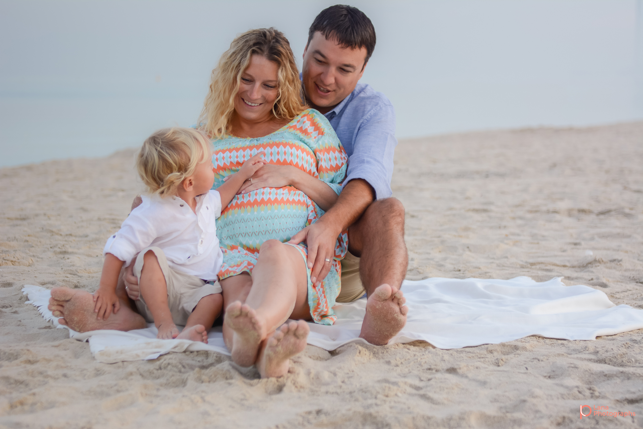 Beach Family and Maternity Session in Dubai portrait of a  family of three posing on the beach in Dubai