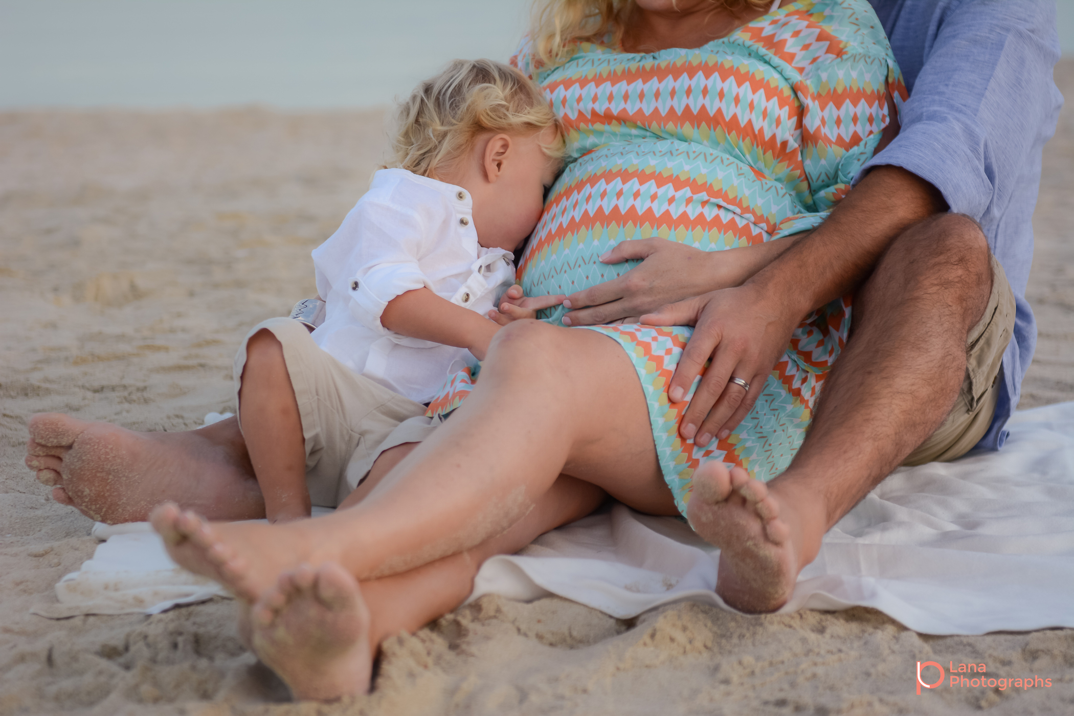 Beach Family and Maternity Session in Dubai little boy snuggling his mother's pregnant belly by the beach