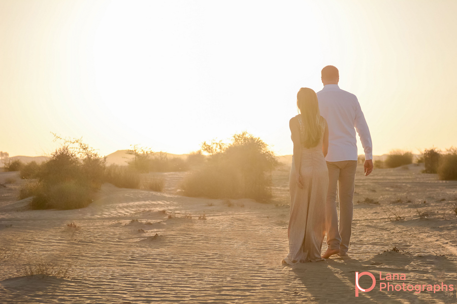 Dubai Maternity Photography portrait of expectant couple walking into the horizon as the sun sets down