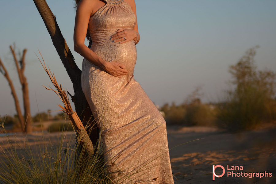 Dubai Maternity Photography portrait of pregnant woman posing against a tree in the desert as the sun sets down