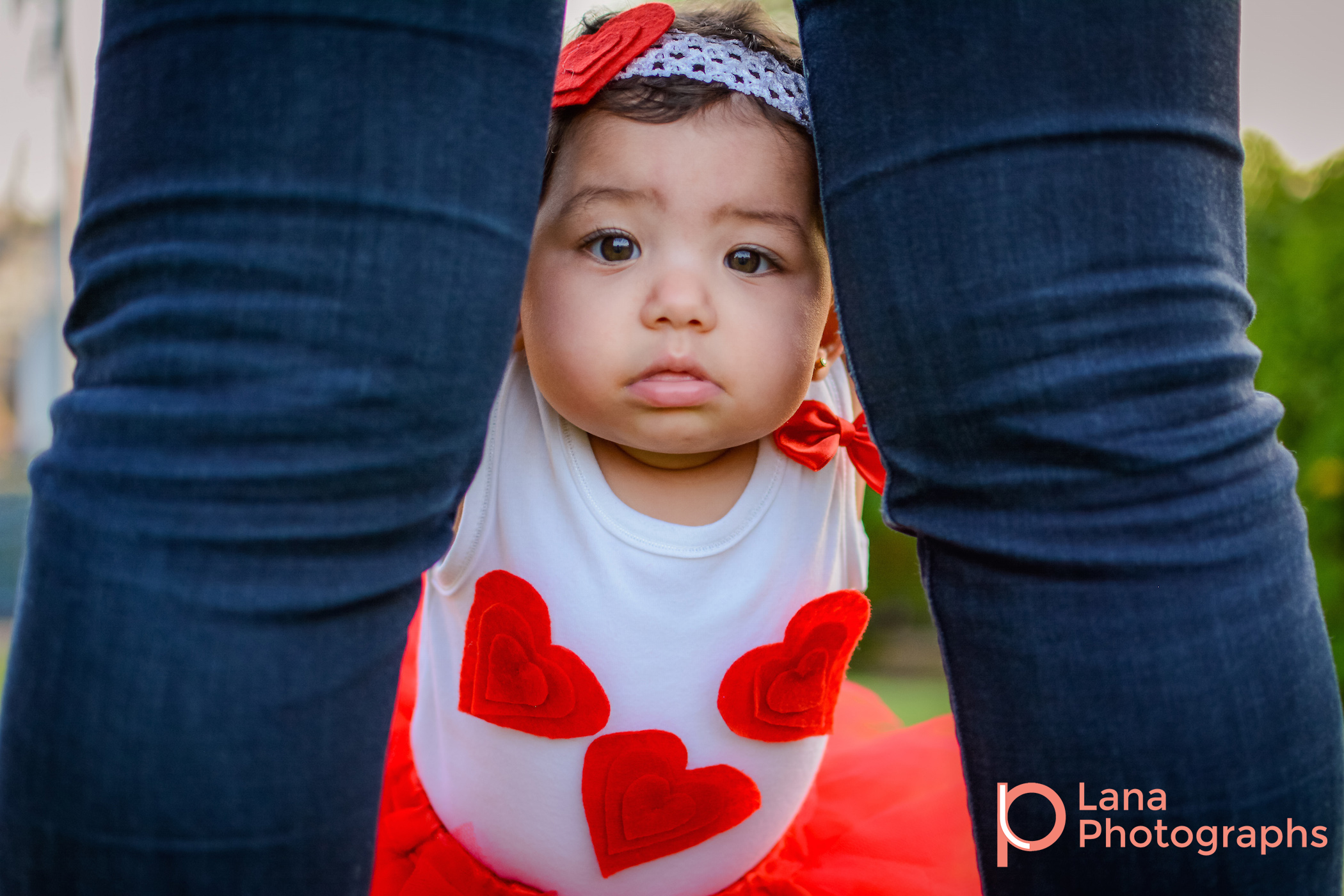 Dubai Family Photography portrait of a little baby girl in red tutu in the park standing between mother's legs