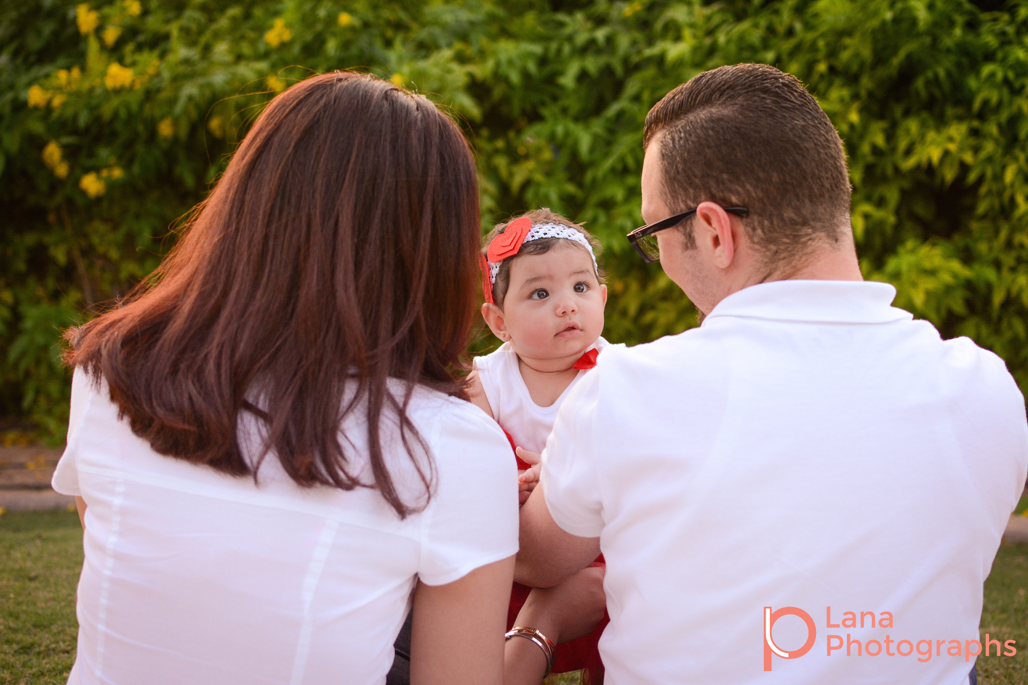 Dubai Family Photography family portrait of a family of three wearing red and white in the park