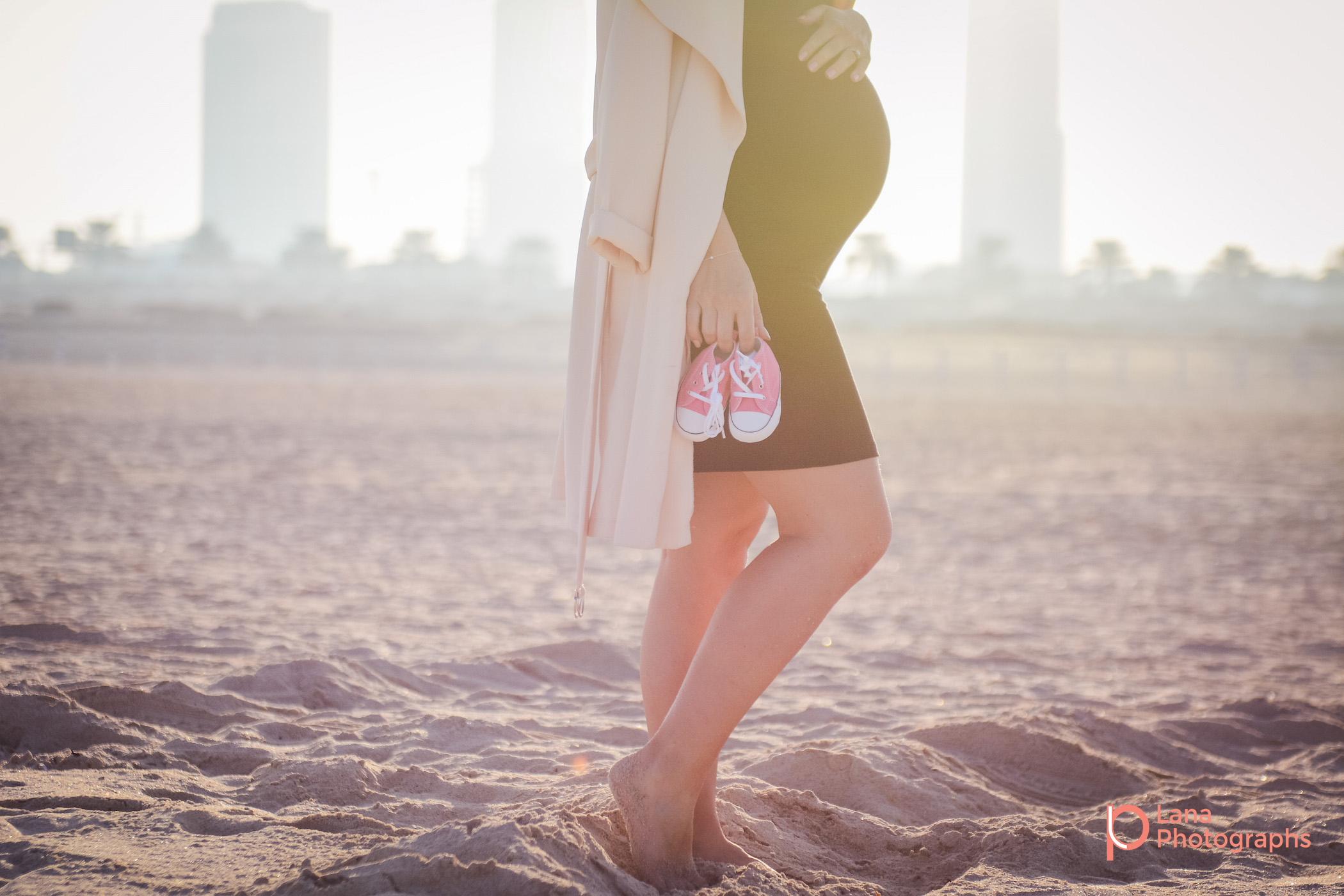 Dubai Maternity Photographer portrait of a pregnant woman walking along the beach while holding her daughter's shoes