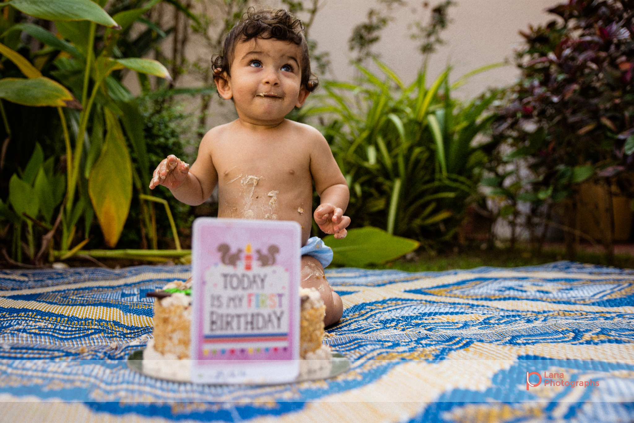 baby boy posing happily with his one year birthday cake outside his home in the garden