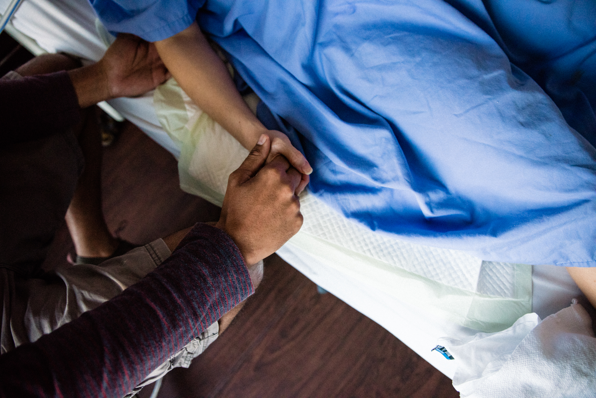 Lana Photographs Dubai Birth Photographer image of man holding his wife's hand while she is in labor inside the labor ward at Dubai Mediclinic City Hospital