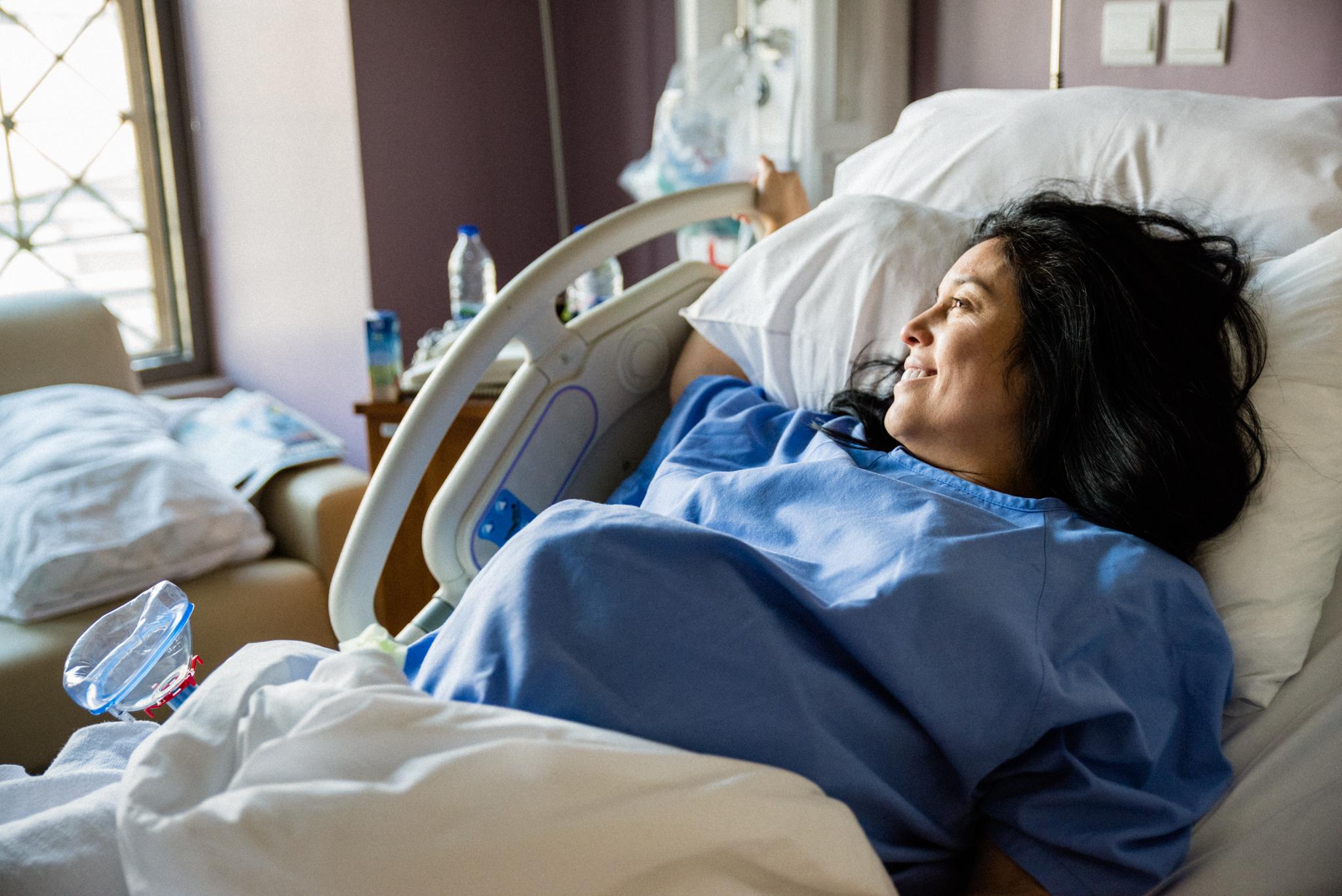 Lana Photographs Dubai Birth Photographer woman resting between contractions during labor inside the labor ward at Dubai Mediclinic City Hospital