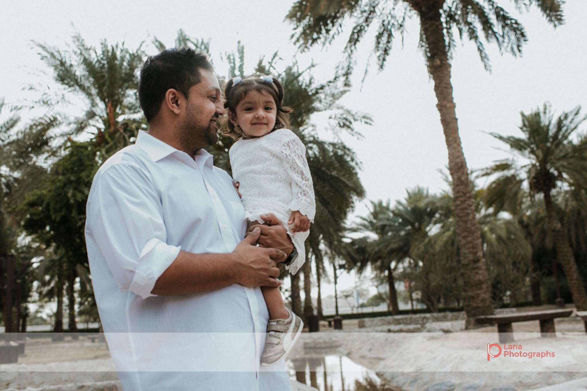 Lana Photographs Family Photographer Dubai Top Family Photographers father carrying girl under palm trees