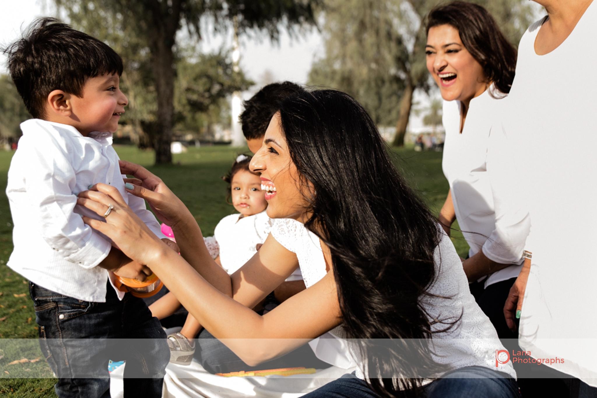 Lana Photographs Family Photographer Dubai Top Family Photographers family playing tickle war in the park